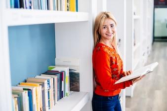 Cheerful woman near bookcase