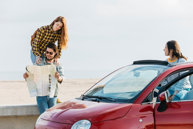 Cheerful woman near man looking at map and lady leaning out from car