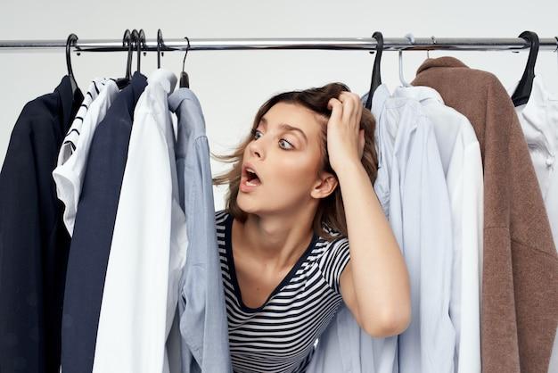 Веселая женщина возле гардероба шопоголик изолированный фон