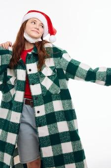 Веселая женщина новогодняя одежда медицинская маска смотрит в сторону светлом фоне. фото высокого качества