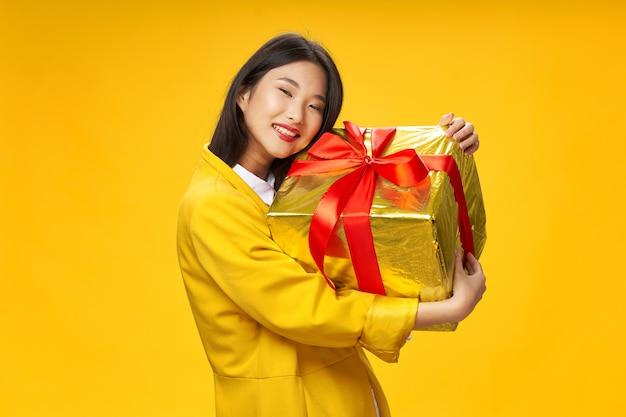 Веселая женщина азиатской внешности с большим подарком