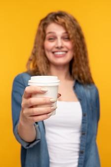 ホットコーヒーの紙コップを提供する陽気な女性