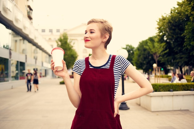 Cheerful woman outdoors walking in glass with fashion drink