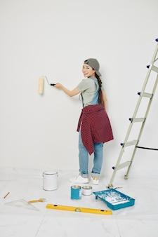 Cheerful woman painting walls