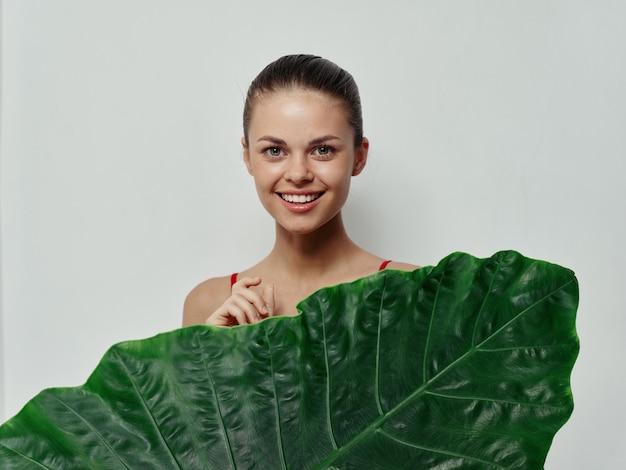 Cheerful woman palm leaf exotic bare shoulders studio
