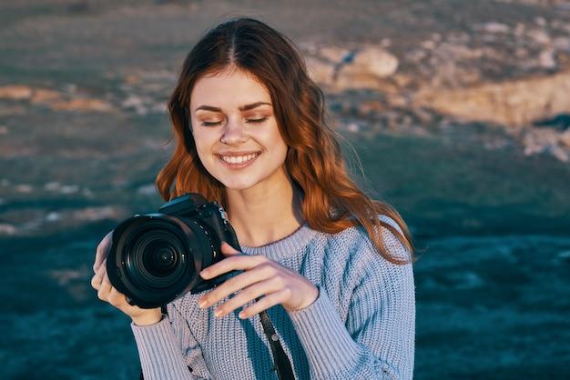 자연 태양에서 그녀의 손에 카메라와 함께 쾌활 한 여자 사진