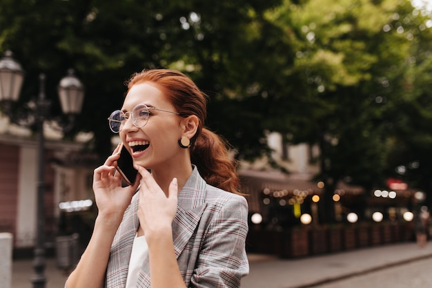 Cheerful woman in plaid outfit and eyeglasses happily talking on phone