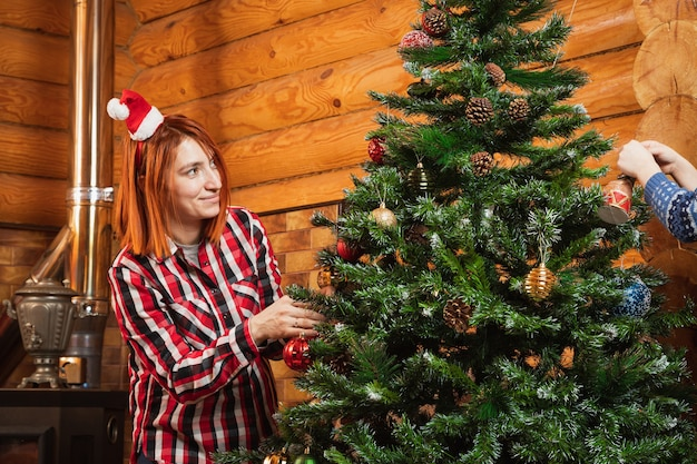 A cheerful woman in a plaid shirt hangs a beautiful shiny ball on a christmas tree oon the background of a lighted fireplace,