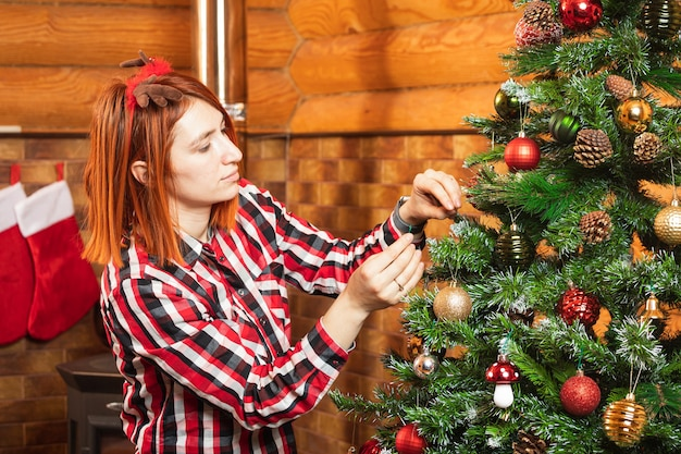 A cheerful woman in a plaid shirt hangs a beautiful shiny ball on a christmas tree