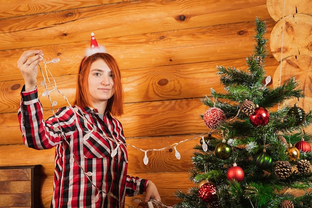 A cheerful woman in a plaid shirt hangs a garland on a christmas tree oon the background of a lighted fireplace