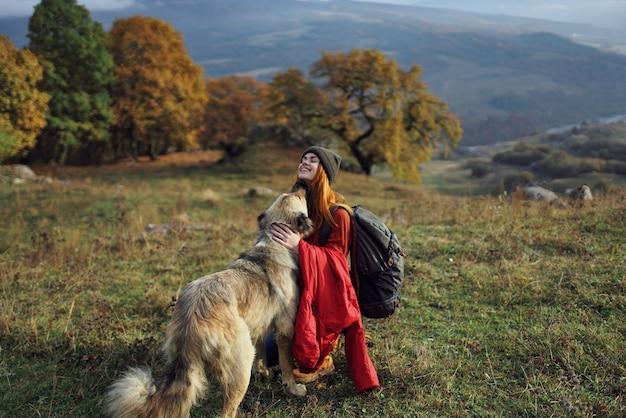 Веселая женщина играет с собакой на открытом воздухе в горы, путешествия, отдых