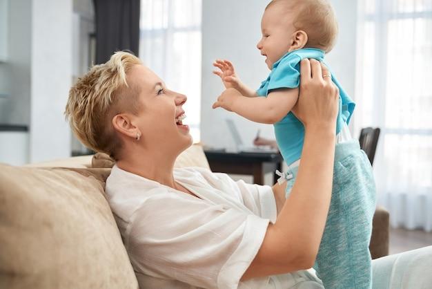 소파에 그녀의 작은 아들과 함께 재생하는 쾌활 한 여자