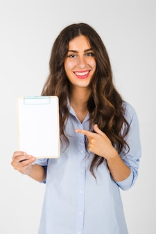 Cheerful woman pointing at clipboard