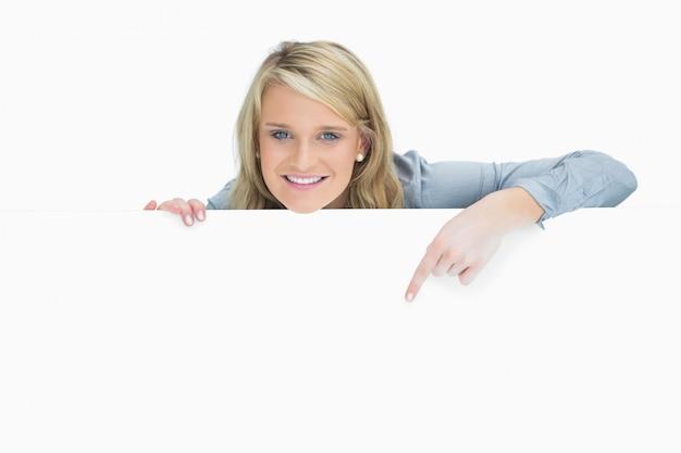 ポスターを指差している陽気な女性