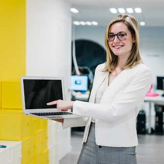Cheerful woman pointing at laptop display