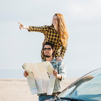 Cheerful woman pointing near man looking at map near car