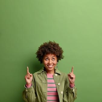 쾌활한 여자는 위의 두 손가락이 녹색 벽 위에 고립 된 세련된 옷을 입고 기꺼이 당신의 광고 미소에 대한 복사 공간을 보여줍니다