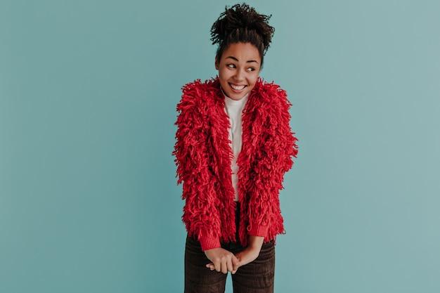 ふわふわの赤いジャケットでポーズをとる陽気な女性