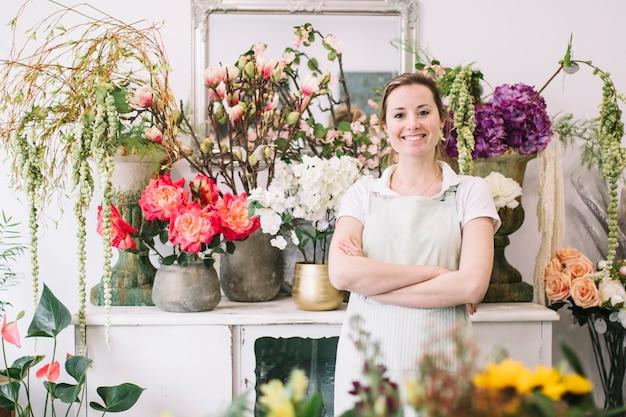 Веселая женщина позирует возле цветов