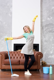 Cheerful woman posing with cleaning mop near couch