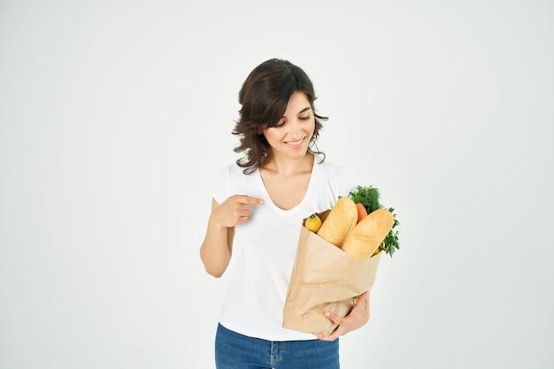 쾌활한 여성은 슈퍼마켓 배달에 식료품과 함께 동일한 문자열 패키지를 긍정적으로 제공합니다. 고품질 사진