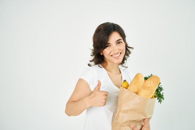 Cheerful woman positive same string package with groceries in supermarket delivery