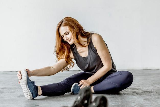 Janusirsasanaポーズを練習している陽気な女性