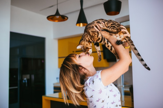 Cheerful woman raises bengal cat up standing in the kitchen