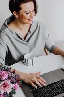 Веселая женщина, читающая книгу на своем ноутбуке
