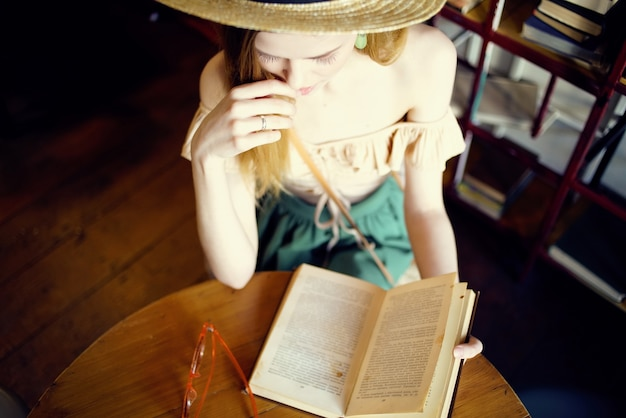 Cheerful woman reading a book in a cafe communication