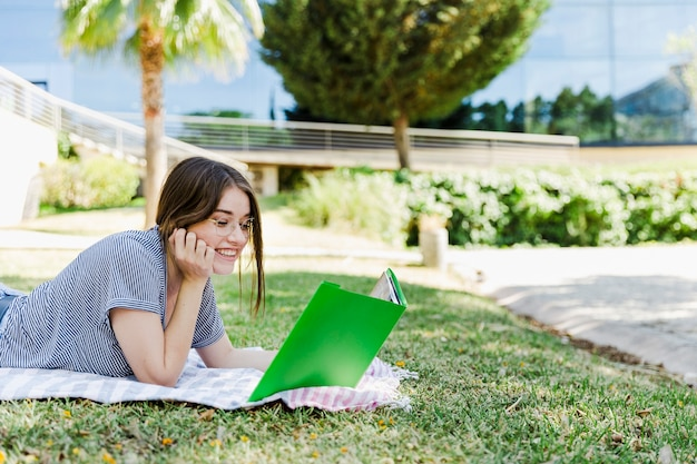 Cheerful woman reading textbook on park grass