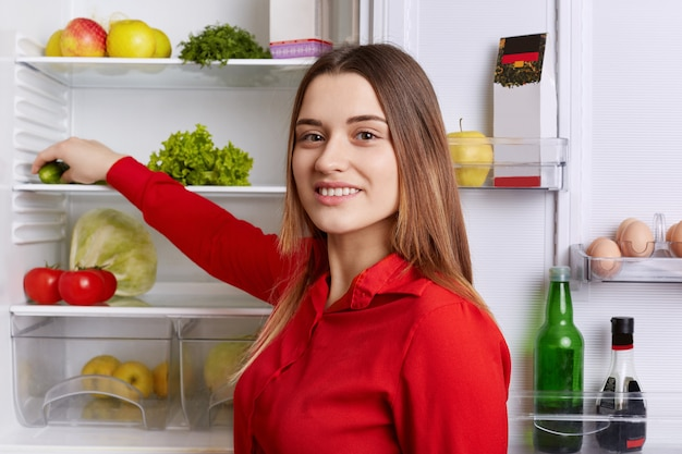 Cheerful woman in red blouse with pleasant appearance stands near opened fridge, choose necessary products for cooking dinner. smiling housewife takes cucumber, poses on kitchen in good mood