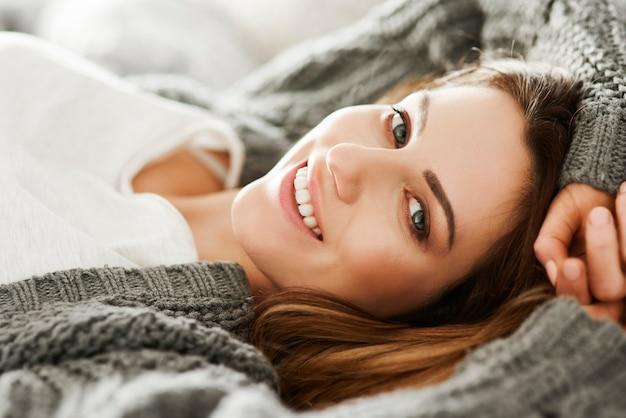 ベッドでリラックスした陽気な女性