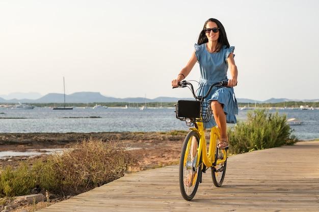 海の近くの堤防に沿って自転車に乗る陽気な女性