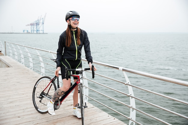 Cheerful woman riding on a bicycle outdoors on the beach
