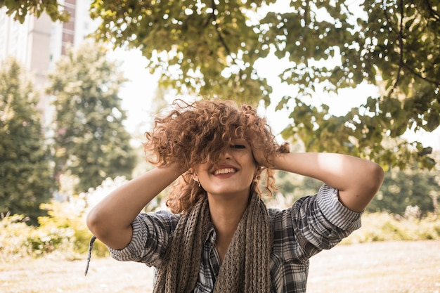 Cheerful woman rumpling hair in park