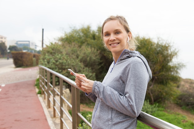 Cheerful woman runner choosing music for outdoor training