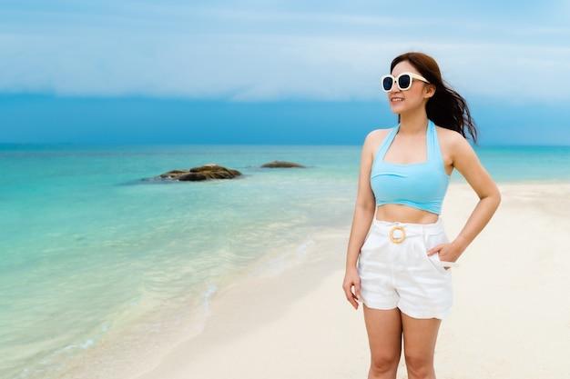 Cheerful woman on the sea beach at koh munnork island, rayong, thailand