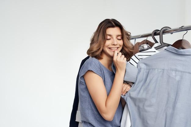 옷장 고립 된 배경 근처 옷의 쾌활 한 여자 선택