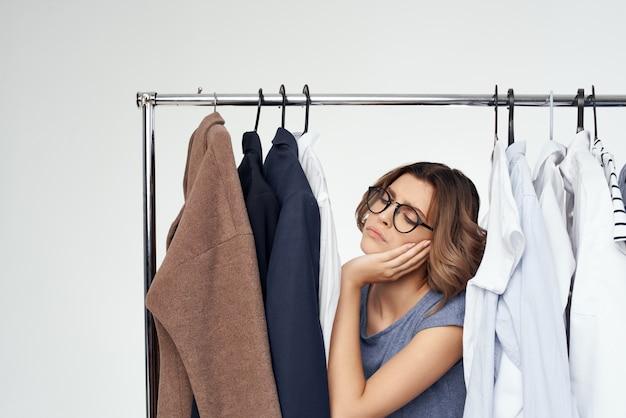 Веселая женщина выбор одежды возле шкафа на светлом фоне