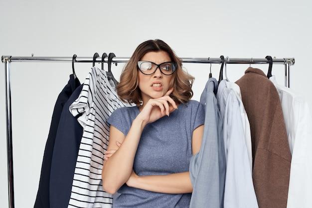 옷장 스튜디오 라이프 스타일 근처의 쾌활한 여성의 옷 선택
