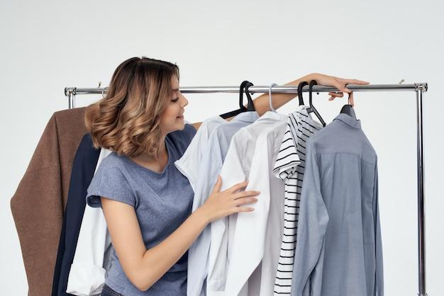 Веселая женщина-шопоголик, выбирая одежду, делая покупки в магазине светлом фоне
