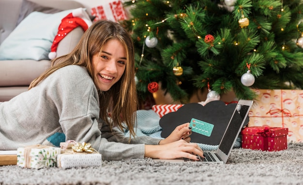 Cheerful woman shopping online and looking at camera