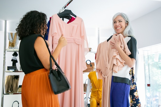 Cheerful woman showing chosen dress with hanger to her friend and laughing. two ladies shopping in fashion store together. consumerism or shopping concept