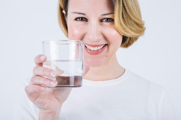 Donna allegra che mostra bicchiere d'acqua