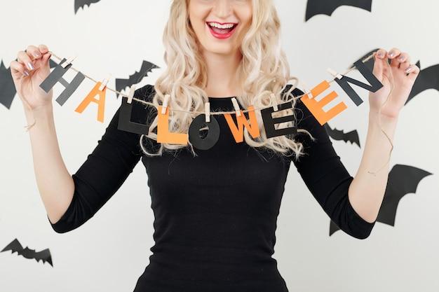 Веселая женщина показывает гирлянду на хэллоуин