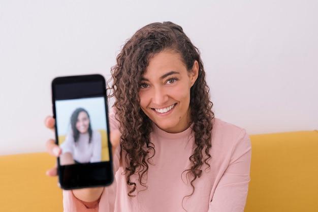 Жизнерадостная женщина, показывая автопортрет на смартфоне