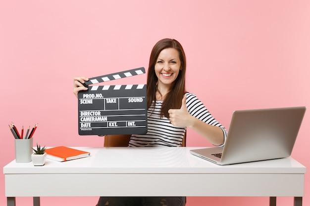 쾌활한 여성이 클래식 블랙 필름 제작 클래퍼보드를 들고 사무실에 앉아 노트북을 들고 프로젝트 작업을 하고 있습니다.