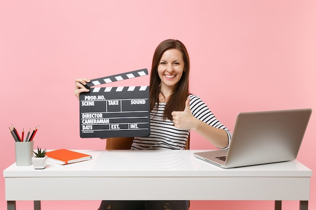 Cheerful woman showing thumb up holding classic black film making clapperboard, working on project while sit at office with laptop isolated on pink background. achievement business career. copy space.