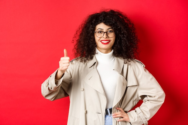 Cheerful woman showing thumbs up and smiling, recommending good thing, standing in glasses and trench coat against red background.